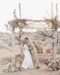 At their desert wedding, Christen and Billy exchanged vows under a structure built with natural wood, protea, and wax flowers, and topped with a crocheted cloth. They now keep the textile in their living room!