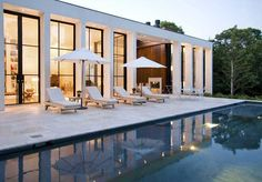 Resting on a five acre property, this fantastic residence displays two contrasting facades – a privacy-protecting front view composed of two volumes resting on a smaller wooden volume and a fully glazed south facade mirroring its 14 feet high steel and glass windows and stucco piers in the nearby pool.