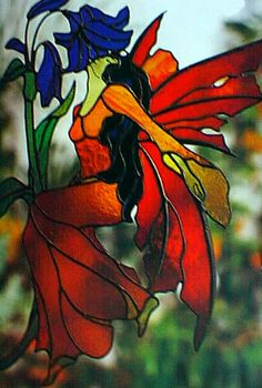 Woman Faerie in red dress with red wings smelling blue flower. Faerie Lights Stained Glass Pattern Book