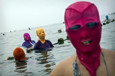 shihlun:  Chinese women wear face-kinis as they walk in to the water to swim at the beach on August 20, 2014 in the Yellow Sea in Qingdao, China. The locally designed mask is worn by many local women to protect them from jellyfish stings, algae and the sun's ultraviolet rays. (Photos by Kevin Frayer/Getty Images)