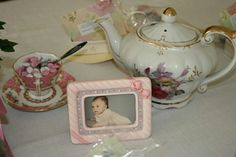 A teapot, m&m' s in a teacup, and a picture of the bride growing up was put on each table.