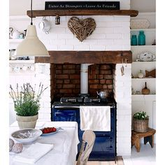 Beams and a range cooker are key ingredients of a classic country kitchen, while crumpled linens and an industrial-style pendant light create a relaxed, modern feel in this coastal kitchen