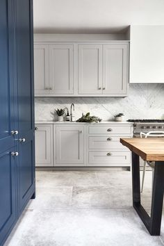 Concrete flooring in the kitchen. Love these shaker cabinetry Blakes London
