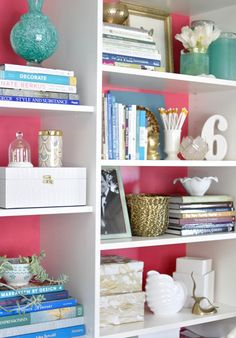 bookcase styling... a solid color behind looks great.  i'd love to do this with deep walnut shelves with a fun, bright pastel color wall.
