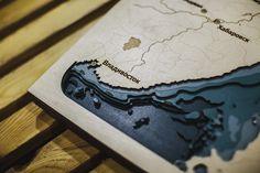 Это дверь в другой мир, который в буквальном смысле лежит ниже лодки. Батиметрическая карта склеена из листов березы, создавая мощный эффект глубины.
