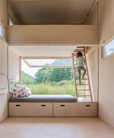 A ladder placed at the end of the platform can be used to access a bed tucked into the space beneath the ceiling. The bed looks down onto the living area and has its own window offering a view of the countryside.