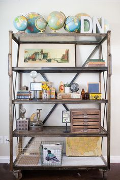 Take advantage of the tops of bookshelves for larger favorites and use high-up shelves to show them off. This bookshelf from Oh, Hello Friend houses several globes without taking up too much real estate.   - HouseBeautiful.com