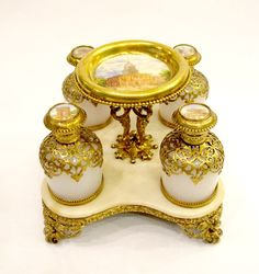 A Palais Royal French circa 1860 perfume set comprising if 4 white opaline scent bottles with miniatures of Paris and a central plaque on ivory. All on a marble base.