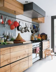 木目調の収納棚がオシャレなモダンキッチン。扉の中にしまいがちなキッチンツールをあえてフックで吊り下げて見えるところに並べて収納。フライパン同志が当たって傷がつくこともないし、探す手間も省けちゃう。主婦に喜ばれるDIYですね。