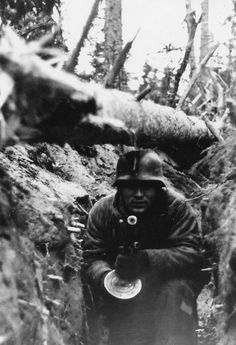 "chocolate-n-vanilla-swirl-irl: "" A German soldier in a trench with a captured soviet PPSH-41 submachine gun on the eastern front. """