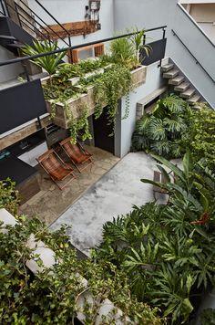 This Slender Concrete Home in Brazil Feels Like an Urban Jungle - Photo 5 of 13 - An outdoor kitchen in the lush, backyard garden aids in entertaining. Concrete Patios, Concrete Backyard, Backyard Garden Landscape, Backyard Landscaping, Backyard Patio, Balcony Gardening, Terraced Backyard, Concrete Houses, Big Garden