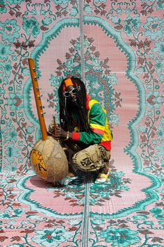 Picture of a musician kneeling next to his string instrument in front of a pink and aqua tapestry-like background