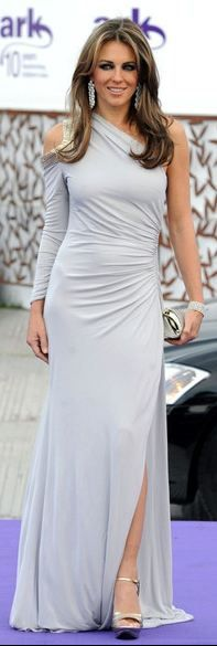 Who made Elizabeth Hurley's gray cut out one shoulder long sleeve gown that she wore in London? Dress – Roberto Cavalli