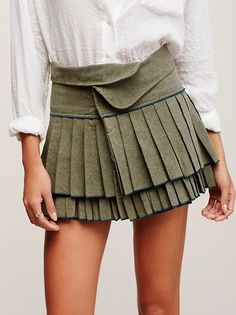 FP One Origami Mini | Pleated cotton mini skirt featuring a tiered hem and contrast seam detail. Rolled waistband with button and hook-and-eye closures make for an easy, effortless fit.