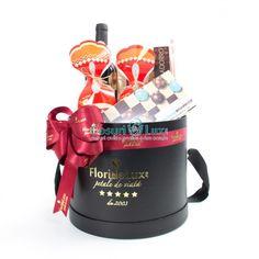 Cos cadou Wine & Sweets, creat intr-o cutie rotunda marca FlorideLux cu 2 cutii fursecuri Secretul Bunicii, Domeniul Anastasia Merlot, cutie Dubletto praline cu cafea, cutie biscuiti cu ciocolata si prajitura de casa Secretul Bunicii cu gem de visine. Ambalarea acestui cos cadou de Paste se face in vid, cu decor amplu fundita satin FlorideLux, logo auriu.