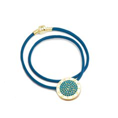 The CJ Golden Charm Leather Necklace Blue Opal Allure alludes femininity,happiness, and suggests an air of unconventionality. Wear it at work, at the office, or out on the town and make a statement! This stunning necklace comes with a blue leather chain with a .925 sterling silver gold tone clasp that connects