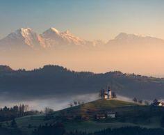 Beautiful winter sunrise illuminating Saint Thomas church near Skofja Loka, Slovenia.
