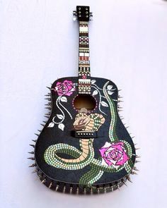 Day of the Dead mosaic guitar with awesome snake and skull graphics with extra large metal spikes all the way around! Meticulously created to catch the light from every direction and create conversation! Front of mosaic guitar has a slithering serpent and beautiful hot pink roses