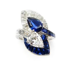 Two stone pear shaped sapphire and diamond crossover ring with leaf shaped clusters,  the 1.45ct sapphire bordered by tapering baguette diamonds and with channel set sapphire shoulder, the diamond bordered by calibré cut sapphires and with channel set diamond shoulder, mounted in platinum. Art Deco or Art Deco style