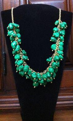 CORRENTE DOURADO, COM PEÇAS VERDES. Essas peças são uma réplica do jade ainda em pedra bruta.