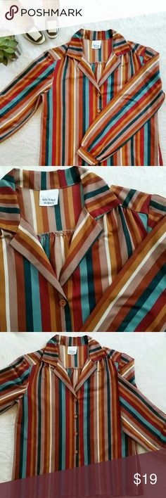 """Vintage Multicolor Striped Blouse This blouse would be amazing if paired with high waisted flared jeans. There is a tag however since it's vintage condition, all printing came off. I'm assuming this is about size medium but please check all measurements before purchasing. Pit to pit is 19.25"""" flat and shoulder to hem is 23"""". There is a tiny defect on the fabric (right shoulder line. Photo 4) and very small (not noticeable when you wear it) snags on few spots on the blouse. Other than that…"""