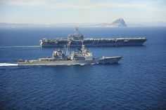 March 31, 2015 - The Ticonderoga-class guided missile cruiser USS Vicksburg (CG 69) escorts the Nimitz-class aircraft carrier USS Theodore Roosevelt (CVN 71) as they pass the Rock of Gibraltar while transiting the Strait of Gibraltar. Theodore Roosevelt deployed from Norfolk and will execute a homeport shift to San Diego at the conclusion of deployment and naval operations.