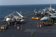 An MD-3A tow tractor is used to maneuver an A-6E Intruder aircraft, left, on the flight deck of the aircraft carrier USS SARATOGA (CV 60) during operations off the coast of Libya. On the right are F-14A Tomcat aircraft and in the center background are A-7E Corsair II aircraft, 12 February 1986. DOD Still Media Photograph: DN-SC-86-05703