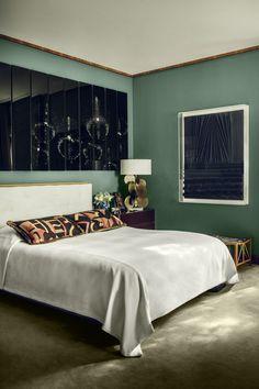 Côté lit, dessiné par Oitoemponto et recouvert de coussins en tissu Hermès, les tables de nuit sont de Jansen, la lampe de chevet une création de Hervé Van der Straeten. Au mur, une photo de Hedi Slimane.