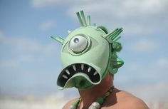 A man with a creature mask walks the playa at Burning Man on the Black Rock Desert near Gerlach, Nev. on Friday Aug. 31, 2012