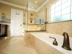Large floor-to-ceiling neutral tiles open up this master bathroom making it seem larger. Glass accent tiles are used as a border around the room and add elegance to the neutral space.