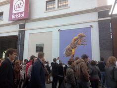 Empleados de Triodos Bank ante un mural de sensibilización sobre el declive de las abejas. Fachada del museo At Bristol.
