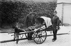 Photograph of two policemen standing alonside an ambulance in which a man is lying, strapped down with handkerchief and hood over his head. Photograph by RL Sirus. 1884