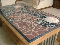 tile mosaic table top, I'm thinking combine this idea with the dining room table made w/ a 4 x 4 pallet. A sheet of thin MDF nailed to the top of the pallet, a 4 x 4 cut in 4 for legs, 2  1 x 6's cut into two and nailed around the edge to provide a edge when grouting and to give it a more finished look.  Cheap dining room table for a college kids first apartment.