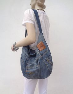 Handmade denim slouchy hobo bag. Rock, Grunge, Boho, Gypsy style.  Made out of a pair of jeans! So, each of the bags has a lot of character and always is unique, one of a kind item. This pair was very interesting medium blue denim with some wash.  Zippered closure. Two functional pockets outside. Printed cotton lining. Inside there is a zipped pocket and an open pocket. Machine washable.  Made of recycled denim. I do my bit to save the Planet :) Always prewashed and surely no marks and…