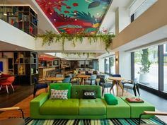 Architecture & Interior Design: Concrete, Amsterdam. The existing building of the former Sky hotel has been stripped completely and has been rebuilt as a 210-key citizenM. The first floor was removed to increase height, light and air in the lobby on the ground floor and the therefore created void now hosts societyM and meeting rooms. A colorful painted art ceiling presents the colors and lush nature that Malaysia is known for. Unique Hotels, Best Hotels, Sofa Design, Interior Design, Coffee Shop Bar, Living Proof, Welcome Decor, Beige Walls, Houses