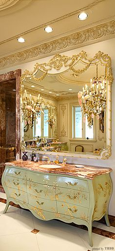 Fabulous decorative French mirror reflects the sparkle of a crystal chandelier in this opulent bathroom.