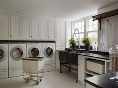 Amazing laundry room features white cabinets paired with black countertops and ceiling height subway tile backsplash. Laundry room with metal dual washstand next to built-in cabinets filled with linen laundry sorter bins as well under wall-mounted clothes Mudroom Laundry Room, Large Laundry Rooms, Farmhouse Laundry Room, Laundry Room Organization, Laundry Storage, Laundry Room Design, Laundry Sorter, Laundry Cart, Laundry Basket