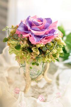 2色のバラの花びらを一枚一枚重ねて大輪のバラに仕上げました。 ガラスの器で透明感あふれるさわやかな印象のアレンジメントです。