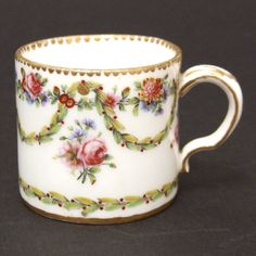 French Soft-Paste PorcelainA Small 18th Century Sèvres Soft-Paste Porcelain Coffee Can. Decorated in the Neo-Classical Style with Swags of Laurel and Garlands of Garden Flowers with Sprigs of Further Flowers. The Base Marked with Interlaced LLs for Sevres, a Date Letter Code `bb` for 1779. Painters Mark `nq` and Incised Provenance : The base with an old French collector`s label. R and G McPherson dealers in antique Chinese porcelain