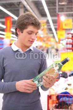 Young man in supermarket with bottle of alcohol