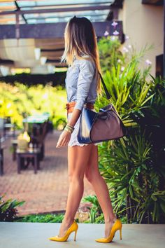 Look do dia casual com bolsa de couro, shorts de renda e camisa feminina