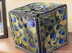 A foam box turns top notch when you cover it from corner to corner…with feathers!  For this look, use hot glue to secure peacock feathers to foam. Then, use classic black cording and flashy  rhinestone ribbon to finish your design.