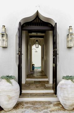Paneled doors with a strong grid design, from E. San Juan, fit into an arched stucco frame; they reference Moorish architecture. Interior Exterior, Home Interior, Exterior Design, Interior Doors, French Interior, Kitchen Interior, Gas Lanterns, Villa, Front Door Decor