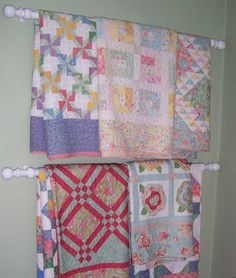 How I display my quilts - wood curtain rods from Pottery Barn Kids, hung on wall on second floor landing.