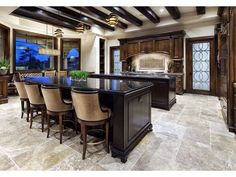 This magnificent kitchen has exposed wood beams, dual islands, and enormous windows to let in tons of natural light.  Source: https://www.zillow.com/digs/Home-Stratosphere-boards/Luxury-Kitchens/