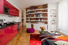 aménagement petit espace : cuisine ouverte sur le salon, tapis rouge, rangements muraux et sol en parquet