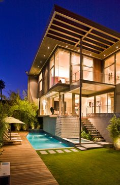 Dream house! Glass, metal, pot lights, wood decking, greenery, pool feature, white washed accents. Great contemporary design!