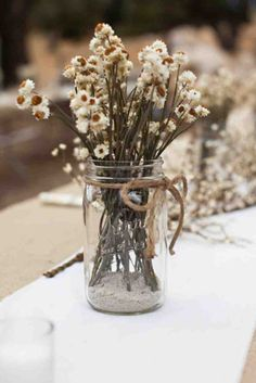 For a super simple wedding centerpiece, gather wildflowers from around your wedding venue and place them in twine-wrapped Mason jars.