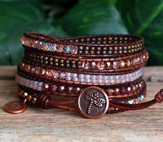 NEW IN THE SHOP! This five wrap bracelet is a charming mixture of a row each of Preciosa Light Rose Fire Polished Czech Beads, glimmering Apollo Gold Fire Polished Czech Beads, and shimmery Golden Mauve Hematite Beads, highlighted by a row each of Matte Tea Rose and Matte Raspberry Miyuki Seed Beads. All are carefully stitched on to top quality Distressed Brown Leather and finished with a sweet little TierraCast Copper Dragonfly Button Closure and TierraCast Copper Lotus Charm. Made with…