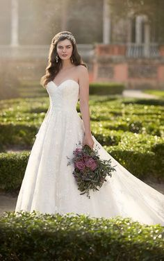 This Essense of Australia traditional A-line bridal gown with ivory or white beaded lace features a fitted bodice, sweetheart neckline, and traditional train. Choose from a corset closure or a zipper closure under crystal buttons.